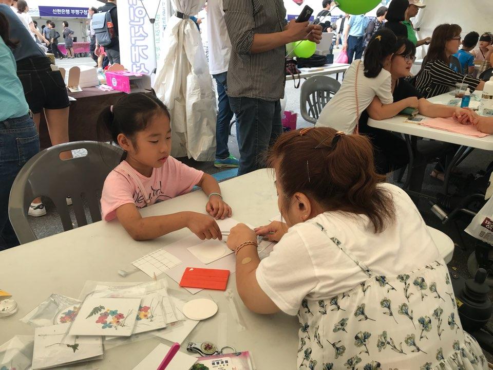 아이가 해밀봉사단과 함께 공예체험(압화 거울만들기)을  집중하여 하고있다.