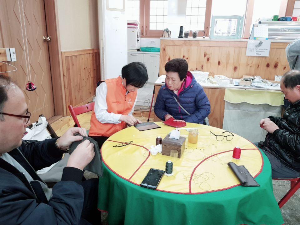 자원봉사자가 참여자에게 바느질을 알려주고 있는 모습의 사진